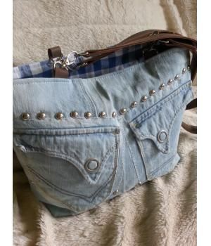 Prachtige schoudertas gemaakt van een spijkerbroek.De tas heeft een afmeting van 40 cm breed en 30 cm hoog.Aan de voorkant twee zakken met een drukknoop waar je je spulletjes in kan doen.De binnenkant is van een blauw geblokte katoen, waar een ritsva...
