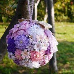 つまみ細工の和装ボールブーケです。ピンク系とパープル系の2色展開です。お選びいただき、ご購入の際に備考欄にどちらか1方をご記入ください。ダリアに菊に桜・・・ ふんわり柔らかな一越ちりめんとなめらかな綸子生地を使って、1輪1輪、花びら1枚ずつ手作りしています。花芯には全てスワロフスキー・クリスタルを仕様しています。パールも全てスワロフスキー社製です。光を受けてキラキラと煌めきます。屋外での前撮りをお考えの方にももちろんおすすめですし、また、屋内の披露宴などでもスポットライトを受ければキラッキラ輝くこと間違いなしです。リボンは落ち着いた金色地に桜模様の織りこまれた西陣織のものを使用。かわいらしさのあるデザインですが、高級感があります。その他のお色、お着物に合わせてのカラーオーダーも承ります。オーダーの場合は、ご注文いただきましてから発送までに1か月程度の制作時間を頂戴致します。ご相談だけでもお気軽に(^^)サイズ:直径 約17cm    花サイズ 直径 約9cm~約…