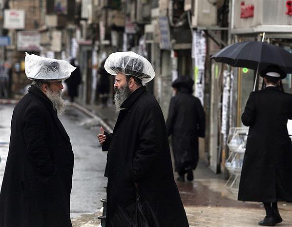 Judíos ultra ortodoxos visten sombreros cubiertos de plástico para protegerse de la lluvia, Jerusalén