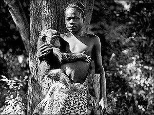 """Ota Benga at the Bronx Zoo in 1906. Only five promotional photos exist of Benga's time here, none of them in the """"Monkey House""""; cameras were not allowed. A sign read;The African Pigmy, """"Ota Benga.""""Age, 23 years. Height, 4 feet 11 inches.Weight, 103 pounds. Brought from the Kasai River, Congo Free State, South Cen- tral Africa, by Dr. Samuel P. Verner. Ex- hibited each afternoon during September"""