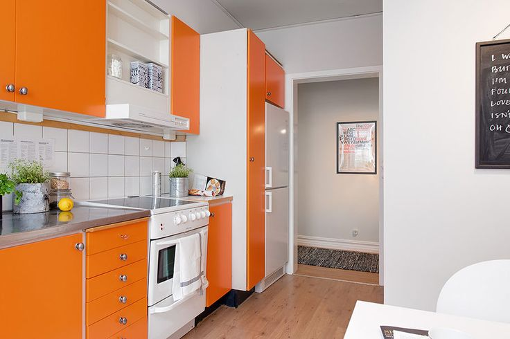 """This hip and fresh apartment is located in Gothenburg, Sweden. While the walls of the home are of a pale gray, it has more vibrantly-toned accents, like the bright orange kitchen, and smaller elements like cushions and wall decorations. Hip and Fresh Apartment in Gothenburg: """"As a parallel street to popular Linnégatan Nordhemsgatan is in a secluded and quiet location in the city heart. It is home furnishing stores, restaurants.."""