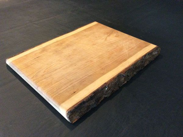 """Cherry cutting board, two live edges with bark, 15"""" x 12"""" x 1"""", priced at $65."""