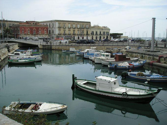 伊シチリア島南東部に位置する古代遺跡の町シラクーサ中心地があるのはオルティジア島でシチリア島本土とは一本の橋で繋がるだけの天然の城塞であった島です本土側の広大な遺跡公園とは一変して幾重もの路地が広がりまるで迷路のような旧市街の町並みが楽しめます観光スポットが多く海の幸に恵まれ南伊独特の活気が溢れています遊歩道沿いでは豪華クルーザーが浮かぶ海を眺めながらゆったりと過ごせます