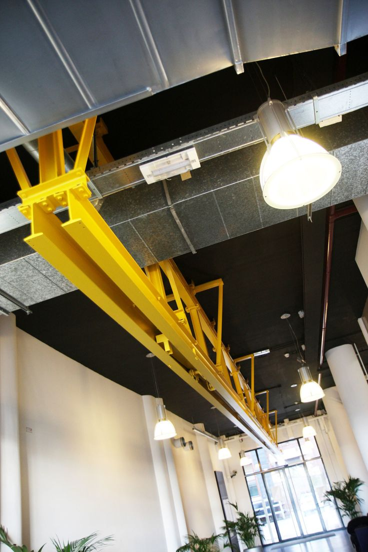 overweldigend industrieel plafond bij entree hal met industriele lampen en gele balk