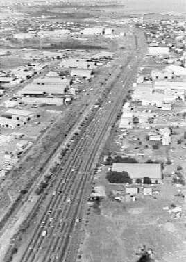 Aerial view looking down Stuart Highway from Bagot Road toward Parap. Shows Bishop Street industrial area, Government workshops, Parap, Stuart Park in distance.1979