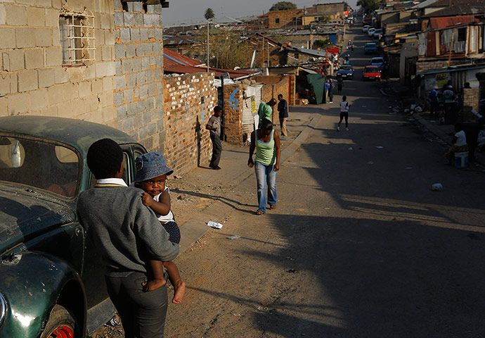 A man carries a young child down one of the streets of the township. In stark contrast to the walled complexes and houses that are a hallmark of middle-class Johannesburg, Alex boasts a colourful environment. Credit: Kim Ludbrook/EPA
