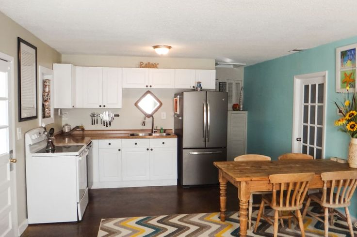 Cozy kitchen has french door fridge, double sink, dishwasher, stove, and large farm house style table. Kiska Cottage-Short walk to beach includes 2 bikes - Houses for Rent in Panama City Beach  #kiskacottage #airbnb #vacationrental #frenchdoorfridge #doublesink #farmhousetable #chevron #cottage #kitchen #remodel #revamp #naturallight