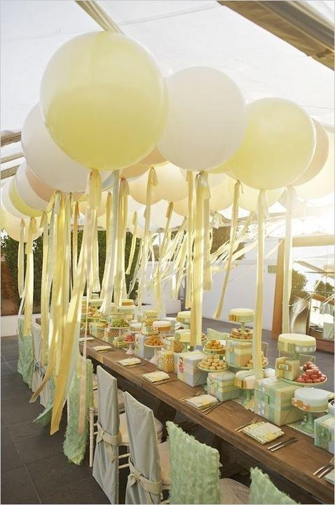 Pale yellow, green and gray shower. Huge balloons with ribbons hanging above table. Beautiful table scape.