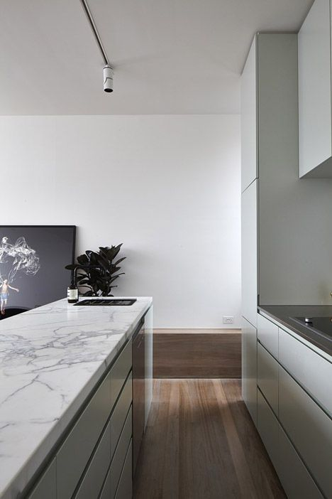 Deep marble work surface with pale contemporary units and wood flooring