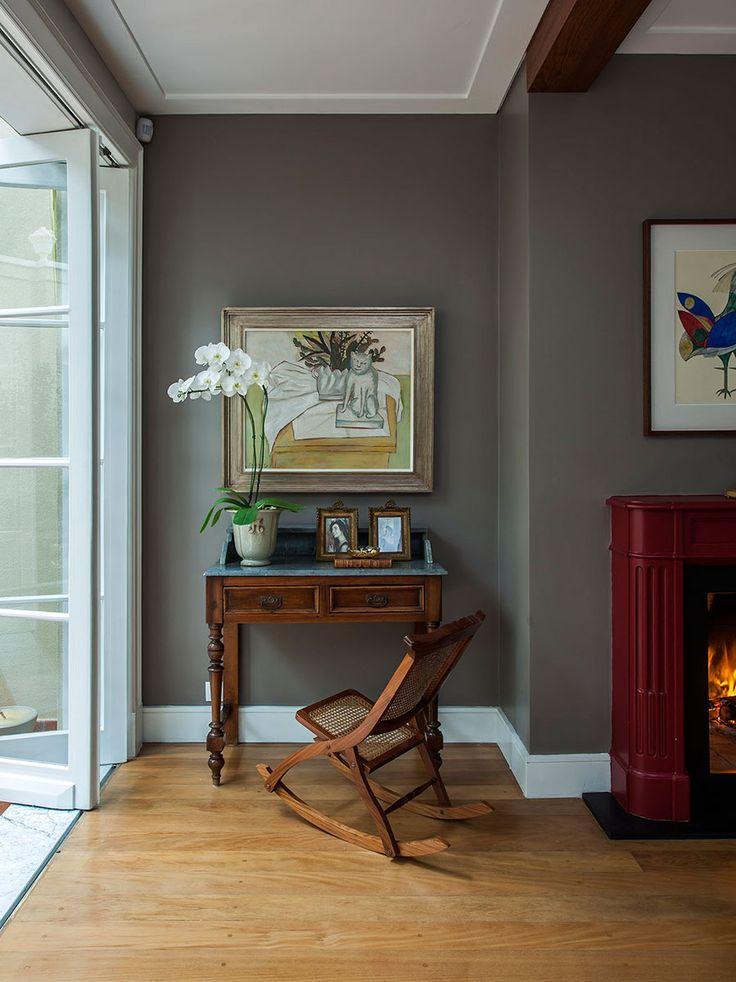 Decoração de casa com móveis antigos e contemporâneos. Parede cinza, quadro, flores, cadeira de madeira e adornos.