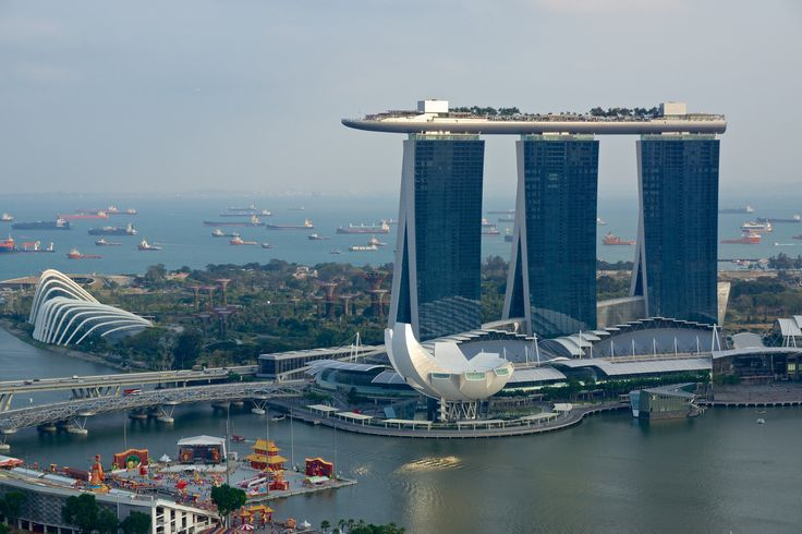 https://flic.kr/p/jYPvxg | Marina Bay Sands hotel, Singapore | In the middle left are the Gardens by the bay with the Flower Dome and the Cloud Forest. In front of the hotel are the Shoppes at Marina Bay Sands and the Art Science Museum. In the left foreground are the Formula 1 grandstand and The Float (at the time this photo was taken used for celebrations for the Chinese New Year welcoming the Year of the Horse). Behind the Float you can see the Helix bridge. In the background you can see…