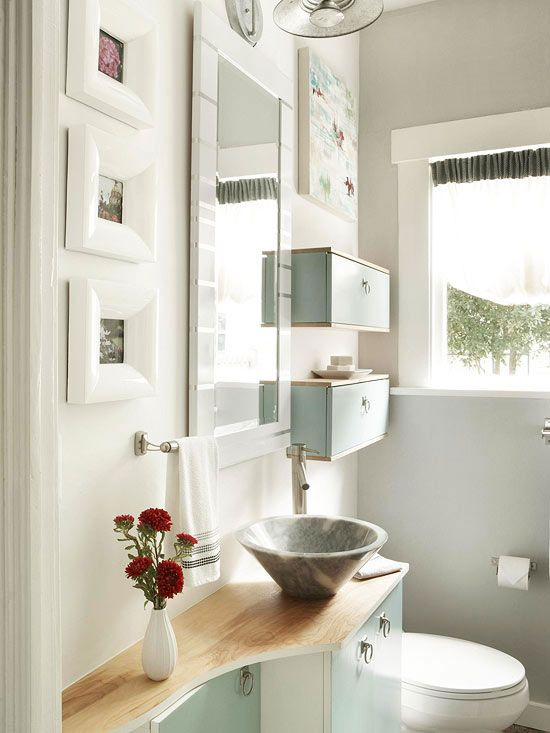 Designed to Fit: This bathroom's ultra tiny construction called for creative storage solutions. The small vanity was constructed using a store-bought cabinet base and a birch plywood countertop. The countertop's curved shape allows the door to open into the small bathroom but still manages to squeeze in more storage. The ring-shape cabinet pulls are small, but they add a dash of vintage charm.