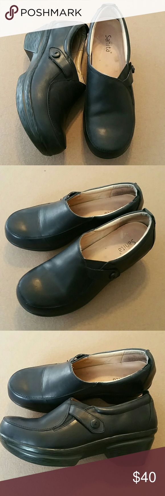 Dansko black leather clogs made by Sanita Sz 41 Dansko clogs made by the Sanita company. Black with a side strap and decorative button over a stretchy elastic expander for easy on and off. These clogs are identical to Danskos. Sanita made them for Dansko up until recently. Excellent pre owned condition. Size 41. No flaws to note. Sanita Shoes Mules & Clogs