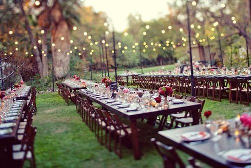 Setting - Dark wood tables against a backdrop of trees beneath the soft glow of lights