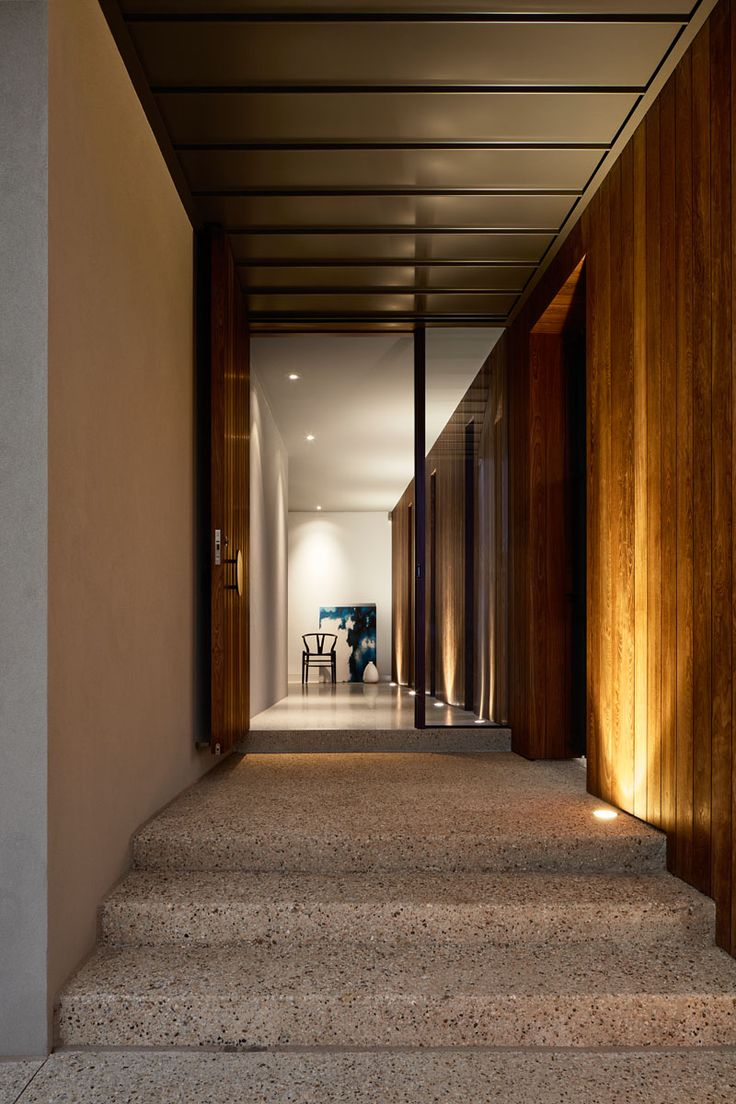 The entryway of this modern house is tucked behind a timber-clad wall with vertical slot windows that frame views of the garden. #Entryway #ModernHouse #Stairs
