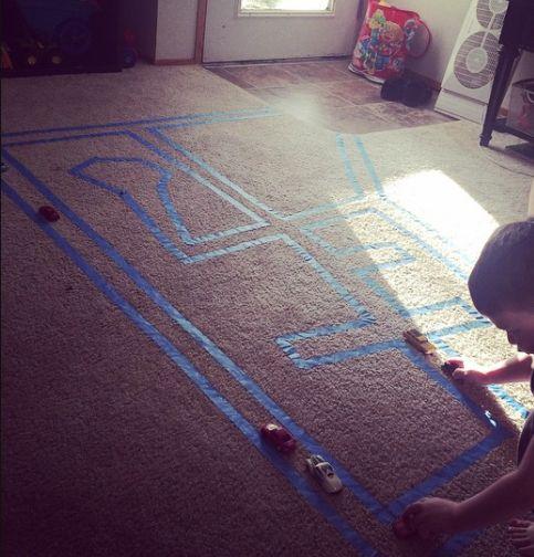 Mit Kreppband kannst du eine Rennstrecke für die Spielzeugautos deines Kindes auf den Teppich kleben.