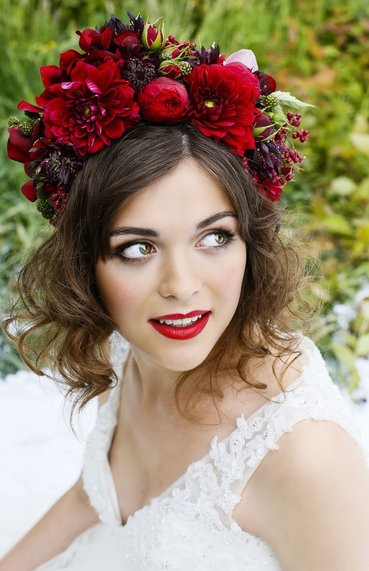 The striking, rich colours of this floral crown, with deep red roses would be perfect for a winter wedding. flowersbykirsty.com