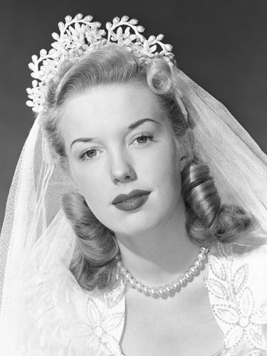 1940 bride wearing the popular Victory Rolls hairstyle named after a plane maneuver used in World War II.