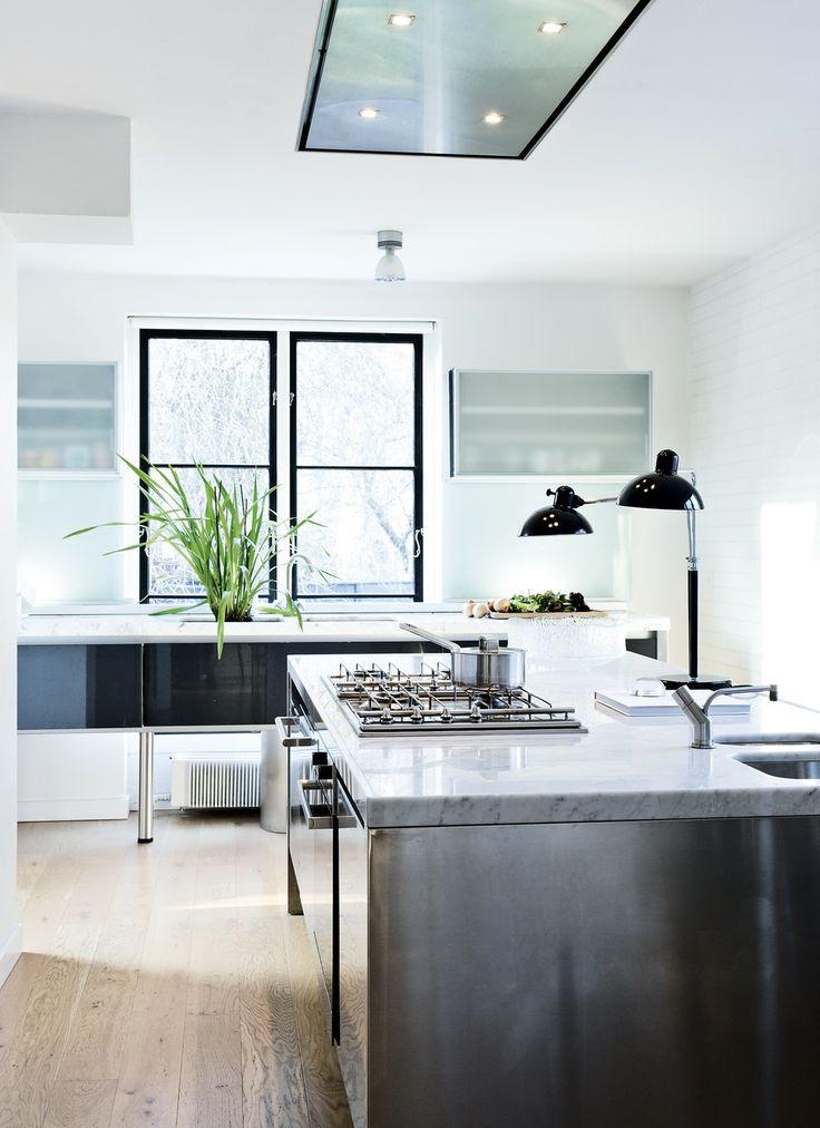 Køkkenet er fra Poliform med mørkegrå låger i højglans, stålfronter og bordplader i marmor. På væggene er opsat hvide fliser fra Aquadomo i et halvstensforbandt-mønster. På køkkenøen står en stor dobbelt bordlampe – en gammel Kaiser Idell.