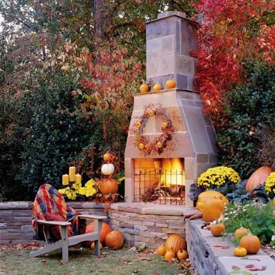 Autumn's Outdoor Room? | A stone fireplace creates the perfect area for fall gatherings in this backyard. A cluster of pumpkins and mums warms up the sitting wall. | SouthernLiving.com