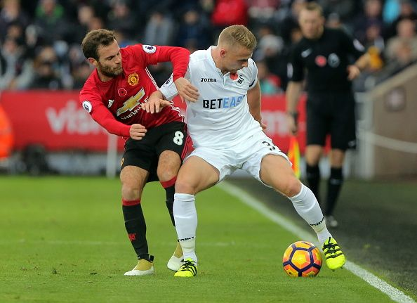 Juan Mata of Manchester United challenges Stephen Kingsley of Swansea City during the Premier League match between Swansea City and Manchester United...