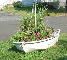 Small dinghy boat turned planter with string lights in a sailboat shape to light up at night.
