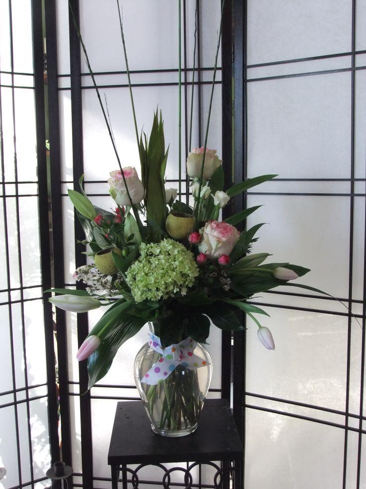Simple Romance- large jardiniere vase, esperance roses, pink tulips, green hydrangeas, pods, spray roses, lilies, aspidistra leaves, wax, sticks & lily grass