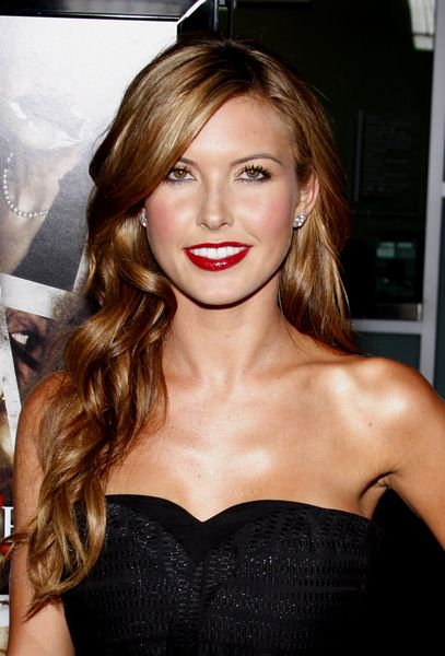 Audrina has lovely soft curls at the Sorority Row Los Angeles Premiere. Audrina Patridge She has pretty golden brown long locks that are styled smooth at the top and then cascade down over her shoulder on one side. The other is pushed toward the back to show off her black strapless dress. Bright red lipstick adds that wow factor. More on Audrina Patridge Long Loose Curls