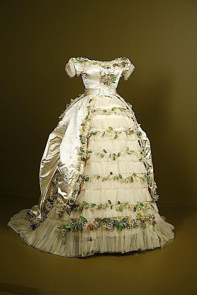 """1869 wedding gown of Elisabeth of Wied, Queen Consort of Romania. Elisabeth's wedding dress shows the emergence of the bustle era. The flounces and over-skirt belong to the crinoline era. """"The dress is made of silk satin, silk tulle with cotton and paper faux flowers."""" (via Fashion Institute of Design and Merchandising - Los Angeles, California USA)."""