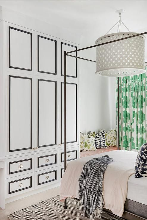 Black and white Hollywood regency wardrobe cabinets are fixed beside a built-in bench topped with a pink cushion accented with green butterfly pillows and black and white geometric pillows.
