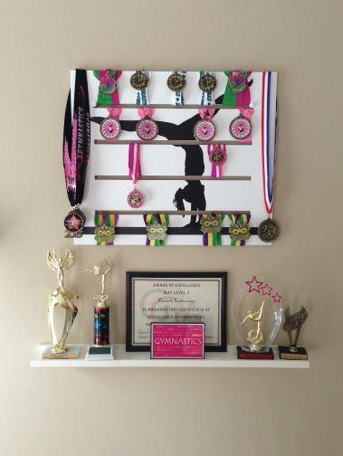 Gymnastics medals display by www.diditmedalsdisplay.com. This is a decorative wall art display that holds up to 40 medals and you can choose from different sports and design.