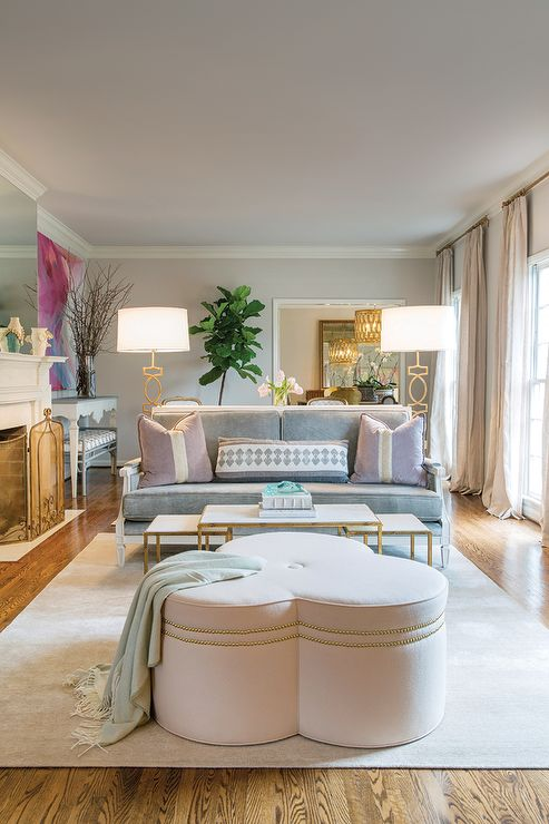 Chic, long living room features two separate sitting areas features one sitting area filled with a gray sofa adorned with lilac stripe pillows facing brass and marble nesting cocktail tables and a pale pink clover ottoman with silver nailhead trim illuminated by a pair of Arteriors Cooper Gold Leaf Iron Floor Lamps.
