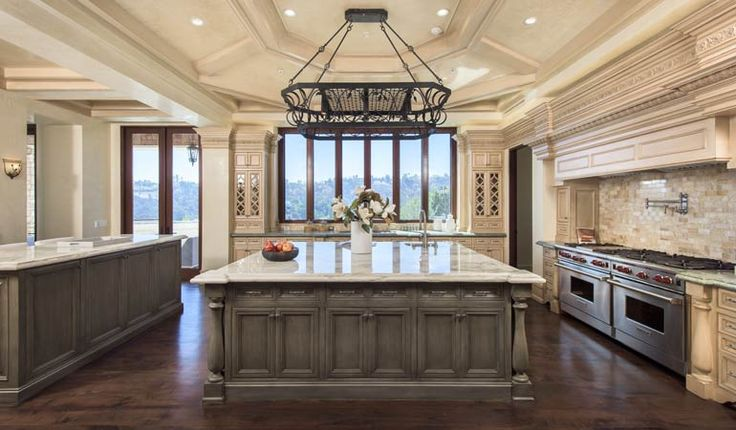 A catering area and butler's pantry connects the dining room to the gourmet kitchen, complete with custom cabinetry, Wolf commercial range and double ovens, dual sinks, commercial size Sub-Zero refrigerator, pantry, wine fridge and a custom kitchen island draped in Persian onyx.