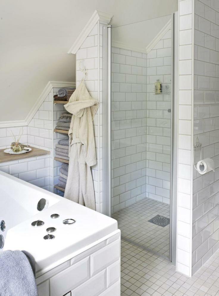 Dusj og badekar er samlet i et av baderommets hjørner. Håndklærne har fått plass i en nisje med eikehyller, dekorativt og praktisk. Under treplaten på benken, ved siden av badekaret, er det skjult oppbevaringsplass.