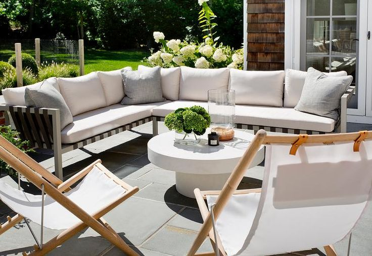 Patio space with outdoor sectional paired with white folding chairs } Tamara Magel