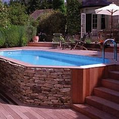 Stone Veneer Pool Natural materials thoughtfully positioned on a sloped site make this aboveground pool appear right at home in the yard. The lesson? To seamlessly blend your pool into the environment, opt for a surround made of local stone or wood.