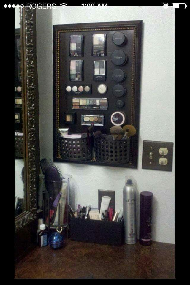 Use an old frame, a metal pan from dollar tree, two small baskets (like the ones to hold your scrubbies next to the kitchen sink) and some stick on magnets. Spray paint metal pan and frame. Attach the two baskets using glue. Put magnets on the back of your makeup to hang up.