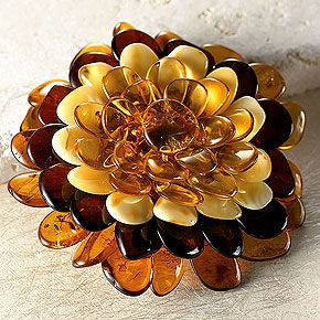 """Amber Flower Pin made from Baltic amber in varying hues woven on a cloth backing, with a silvertone clasp. 2.25"""" in diameter  Smithsonianstore.org"""