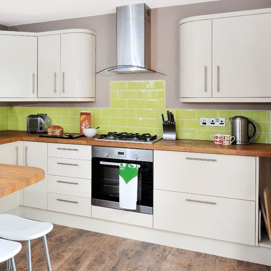 Cream modern kitchen  Cream high-gloss units teamed with warm woods and a zingy lime splashback fuse country and contemporary styles in this kitchen.