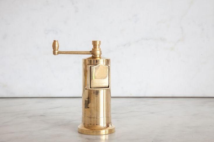 Cast brass pepper mill with a front loading mechanism