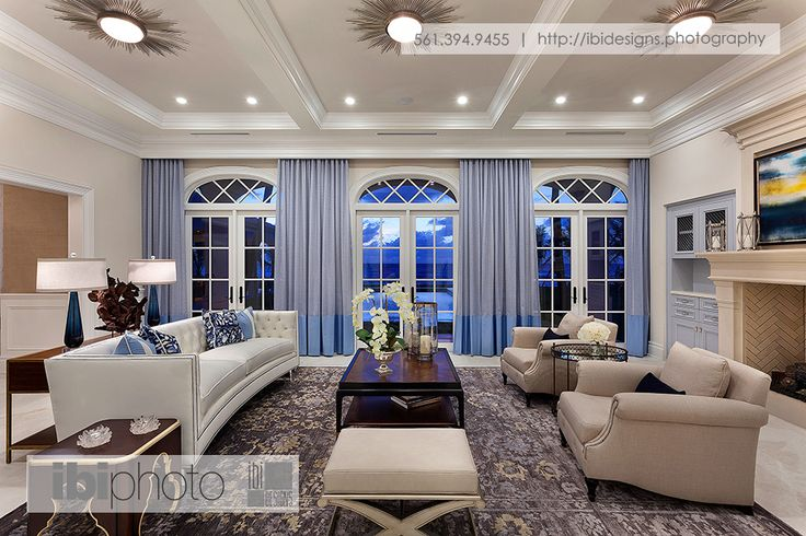 A beach themed color scheme for an oceanfront property. Using shades of blue with tints of brown and subtle hints of white develops a natural atmosphere for a living room. Accents such as end tables, lamps, and decorative items in shades of blue and brown enhance the cozy atmosphere in front of the fireplace. #colorscheme #fireplace #oceanfront #decor