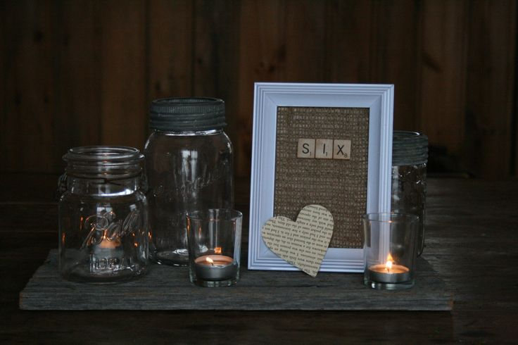 Barn board base. Three vintage mason jars. Scrabble table number in white frame on burlap. vintage novel heart cut out. Candles in votive holders. Flowers in all three mason jars would look beautiful! www.facebook.com/...