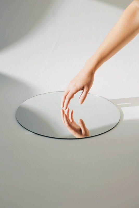 soft touch - round mirror minimal image with a gentle persons hand