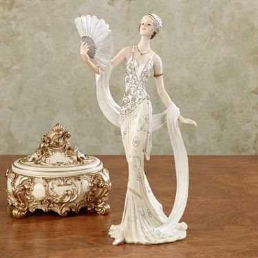"$46 Parisienne Glamour Lady Figurine - The sultry elegance of the Parisienne Glamour Lady Figurine displays the cultured refinement of a lovely woman from the City of Light. Resin figurine features a lady standing with a scarf draped around her arms while holding a fan up with her right hand. She is wearing an ivory dress and stylish hat accented with gray flowers that are covered in gold glitter. Her fan also has glitter. Parisienne lady figurine measures 8.5""Wx4.5""Dx13""H."