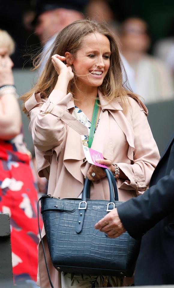 Kim wore a tropical print dress with a pink jacket and blue Aspinal of London handbag