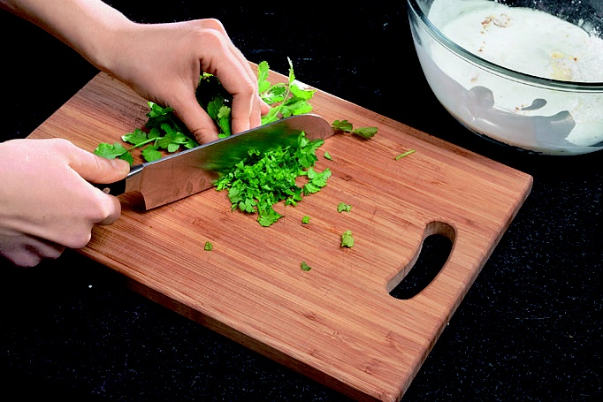 Листья кинзы измельчили ножом, добавили в миску к тесту и все тщательно перемешали вилкой.