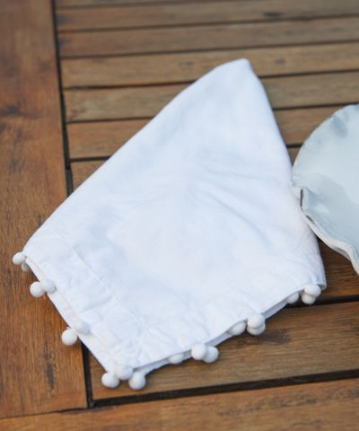 Pom Pom Napkin - White - Easy-care white cotton napkins are always polished and pristine - but these add a playful touch with their edging of pom-pom braid.  The transitional snow-white napkins are ideal for bringing your personal creative flair to a chic white-on-white setting, but colorful plates and chargers let the texture of the bobble edging show, making this sophisticated napkins a perfectly versatile choice.