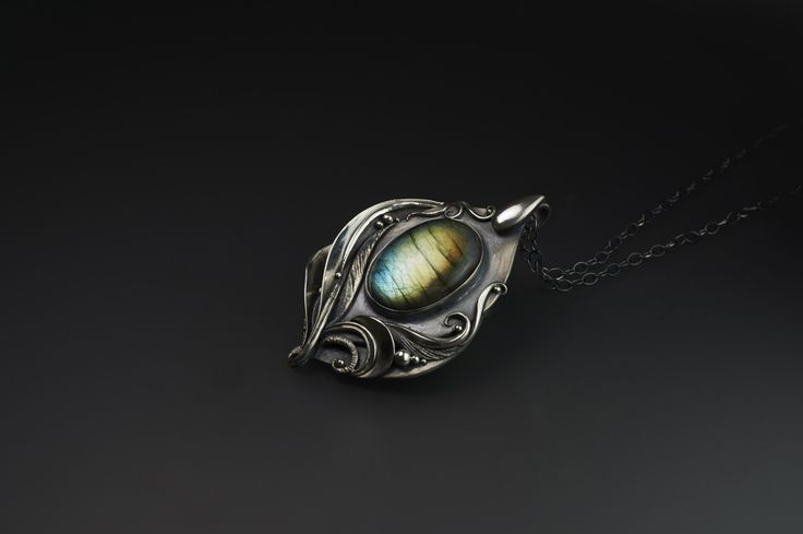 """Flourish - Fine Silver Pendant / Labradorite by Rodi Frunze. This wonderful handmade .999 fine silver pendant produces a dramatic statement with its' amazing Labradorite gemstone. This gemstone produces a gradient of green, to gold, to blue flashes depending on the viewing angle.  When you're by my side, the sun feels warmer.  When you're in my arms, the moon lights our path. When you're in my heart, we """"Flourish""""! - Styve"""