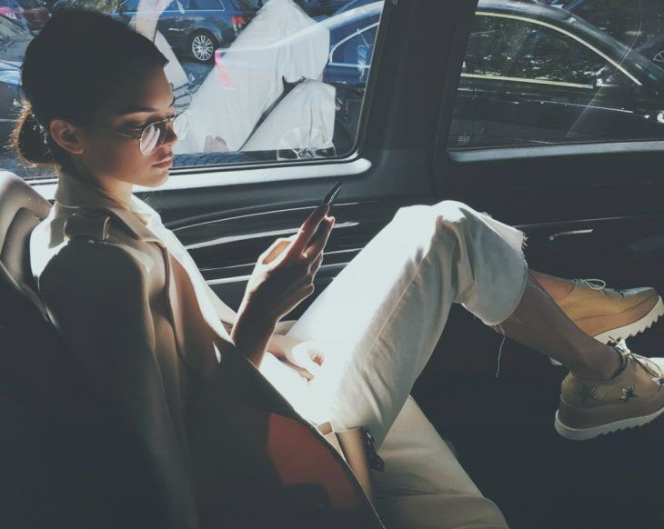 chica sentada junto a ventana de coche con su celular