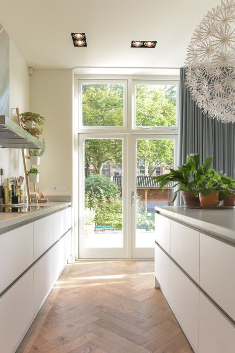 Strakke witte tijdloze keuken in totaal gerenoveerde jaren 20 villa. Mooi in combinatie met de eiken visgraadvloer, strak stucwerk en grote openslaande tuindeuren. www.pieterdeboer.com